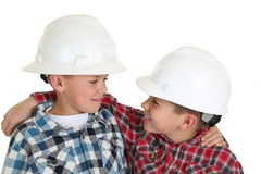 Two boys hugging in construction hard hats Stock Photos