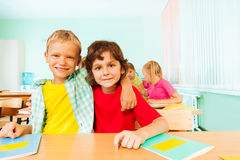 Two boys hugging and sitting together in classroom Royalty Free Stock Photos
