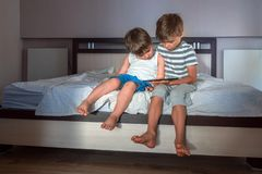 Children and gadgets. Two boys with tablet on the knees. Home schooling concept. Preschooling background. Home stock photos