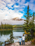 Two boys in Jasper Park. Concept of active vacation and tourism. Morning in the Rocky Mountains, Jasper Park. Two boys looking at a lake holding hands Stock Image