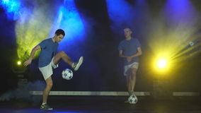 Two boys juggling ball. Two young boys juggling a soccer ball stock video footage