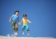 Two boys jump on sand royalty free stock photo