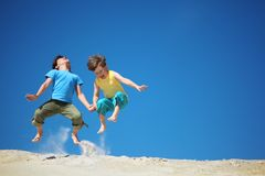 Two boys jump on sand Stock Images