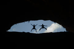 Two boys jumping at the entrance of the Hoq Cave, Socotra, Yemen, joy, happiness Royalty Free Stock Image