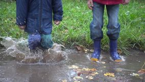 Two boys jumping in muddy puddle, slow motion 250 fps. Two boys jumping in autumn muddy puddle, slow motion 250 fps stock video footage