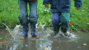Two boys jumping in muddy puddle together, slow motion stock video footage