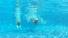 Two Boys Jumping Into Pool Then Swims Underwater To Camera. View from surface of pool as two boys dive in before switching to underwater viewpoint where he swims stock video