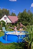 Two boys jumping and splashing in swimming pool Royalty Free Stock Photography