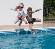 Two boys jumping into swimming pool. Two happy brothers jumping into swimming pool Royalty Free Stock Photos