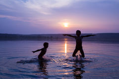 Two boys jumping into water on sunset Royalty Free Stock Image