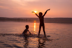 Two boys jumping into water on sunset Royalty Free Stock Photography