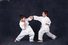 Two boys of the karate in a white kimono battle stock photos