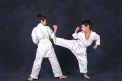 Two boys of the karate in a white kimono battle royalty free stock photos