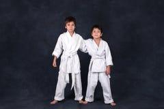Two boys of the karateka in a white kimono stand and smile royalty free stock photo