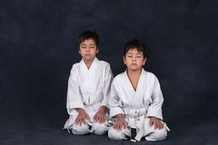 Two boys of the karate in a white kimono. Sit and relax Stock Photos