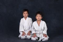 Two boys of the karate in a white kimono stock photos