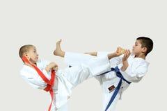 Two boys in karategi are beating blows kicks Royalty Free Stock Image