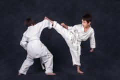 Two boys of the karateka in a white kimono battle. Two boys of the karate in a white kimono battle or train Stock Photo
