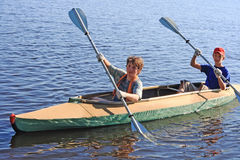 Two boys on a kayak. Two teenagers floating on lake in a kayak Stock Photography