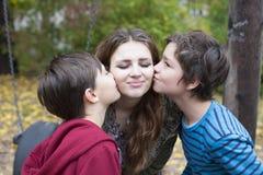 Two boys kissing a teenage girl Stock Image