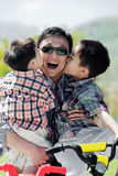 Two boys kissing their father's cheeks. While he holds them in his arms Stock Images