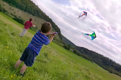 Two boys with kites. Two young boys flying their kites in a meadow Royalty Free Stock Photo