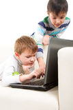 Two boys with laptop. On the sofa Royalty Free Stock Photos