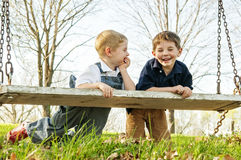 Two boys laughing on swing Royalty Free Stock Photo