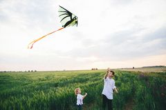 Two boys launching a kite on the wheat filed background. Brotherhood conception royalty free stock image