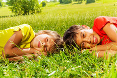 Two boys laying on the grass together in park Stock Image