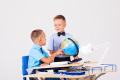 Two boys are learning globe for desk at school stock photo
