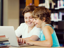 Two boys in library. With notebook Royalty Free Stock Image