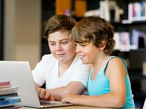 Two boys in library. With notebook Royalty Free Stock Photography
