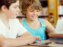 Two boys in library. With notebook Royalty Free Stock Photos