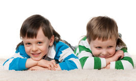 Two boys lie on the carpet. Two cheerful little boys are lying on the carpet; on the white background stock image