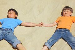Two boys lie on sand with closed eyes Royalty Free Stock Images