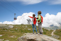 Two boys are looking at cable car in mountains Royalty Free Stock Image