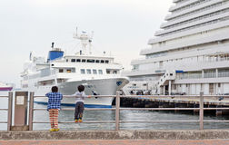 Two boys looking at cruise ship docking at Luxury five-star Kobe Meriken Park Oriental Hotel, Kobe Meriken Park, Port of Kobe, Hyo Stock Image