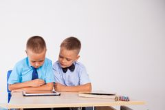 The two boys are looking at Internet Tablet school. 1 Royalty Free Stock Image
