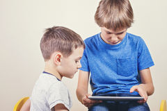 Two boys looking at tablet computer. Education, learning, technology, leisure concept Stock Photography