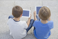 Two boys looking at tablet pc. Childhood, education, learning, technology, leisure concept Royalty Free Stock Image