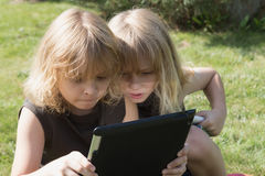 Two boys are looking to the tablet outdoors Stock Image
