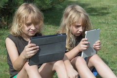 Two boys are looking to their tablets outdoors Royalty Free Stock Images
