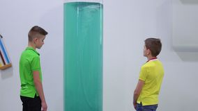 Two boys looks at artificial whirlpool in the museum of popular science. Two boys are looking on the artificial whirlpool inside a big flask. The children stock video footage
