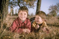 Two boys lying on autumn park Royalty Free Stock Photos