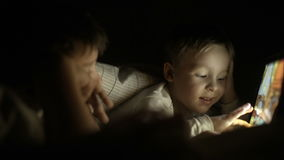 Two boys lying in bed at night and using pad. Two boys using touch pad lying in bed at night. Bright screen enlighting their faces stock video footage