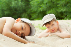 Two boys  lying down on the sea beach Stock Images