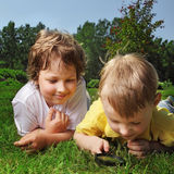 Two boys with magnifying glass Royalty Free Stock Photo