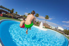 Two boys make a cannonball into the pool Royalty Free Stock Photography