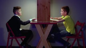 Two boys makes fun in front of each other. Sitting at the table and turning on and off their lights. The museum of popular science and technology. Prores codec stock video footage